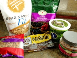 Frozen Greek yogurt bar ingredients. Chopped pecans, granola, dark choclate chips, frozen triple berry blend, Greek yogurt, almonds.