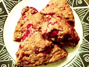 Four whole-wheat raspberry scones on plate.
