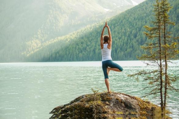 yoga next to mountain lake
